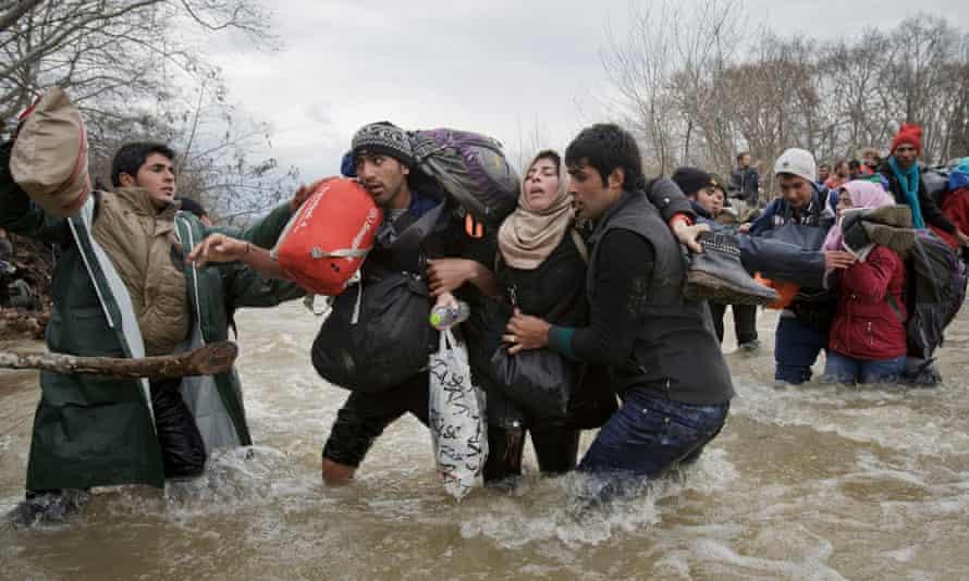 Migrants cross a river