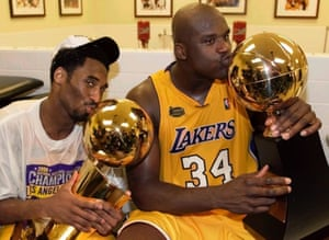 Los Angeles Lakers center Shaquille O'Neal (R) kisses the Most Valuable Player trophy as teammate Kobe Bryant kisses the NBA championship trophy as they celebrate in the locker room after winning the NBA Finals against the Indiana Pacers, June 19, 2000.