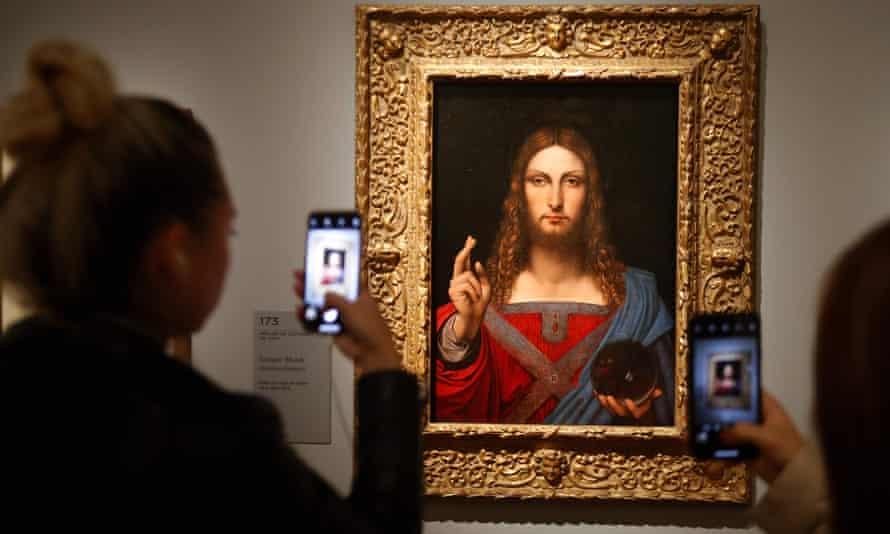 People take pictures of Leonardo da Vinci's Salvator Mundi.