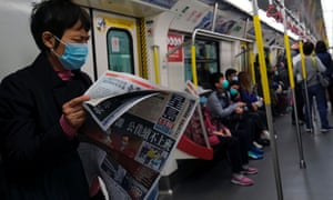 A passenger reads news about a new coronavirus outbreak during a train trip in Hong Kong