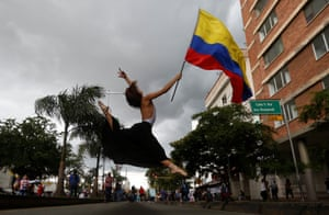 A ballet dancer holding a flag mid-leap at a protest in Cali, Columbia