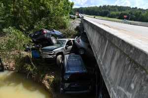 Cars are piled against a bridge, having been swept away.