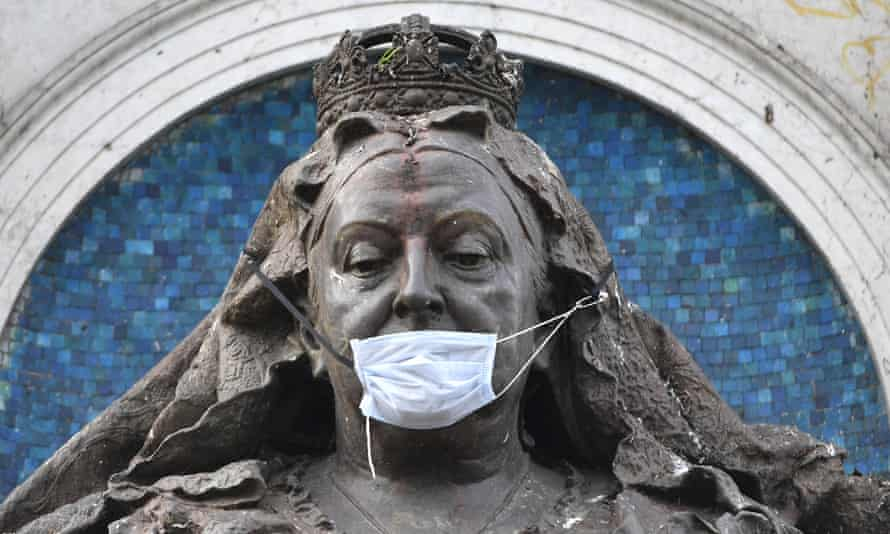 A statue of Queen Victoria adorned with a face mask in Manchester.