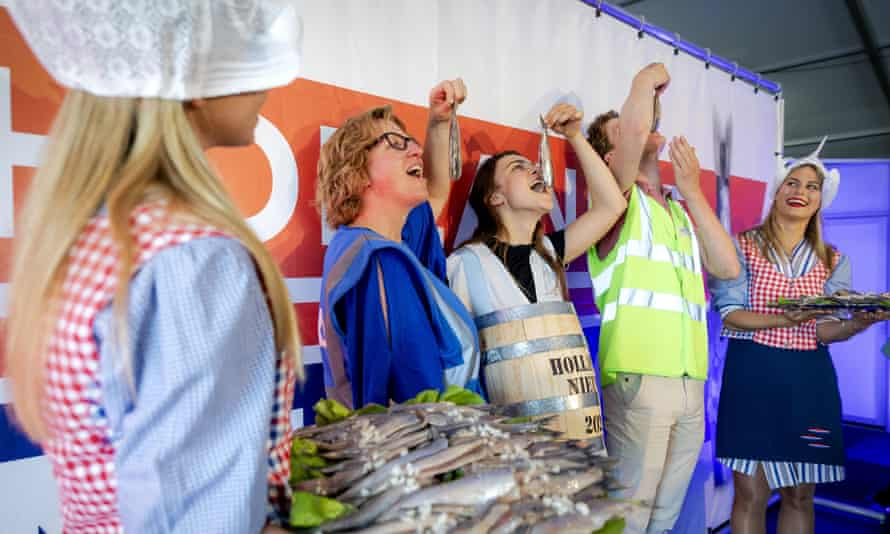 Workers at a vaccination centre in the Hague enjoy a Hollandse nieuwe, or new-season Dutch herring