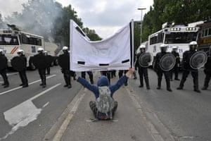 A man sits on the ground and holds a banner in front of Belgium's riot police .