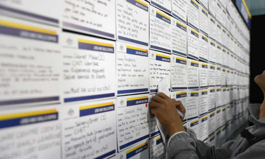 A job seeker takes notes as he browses job notices at a jobs and skills expo run by the Australian government