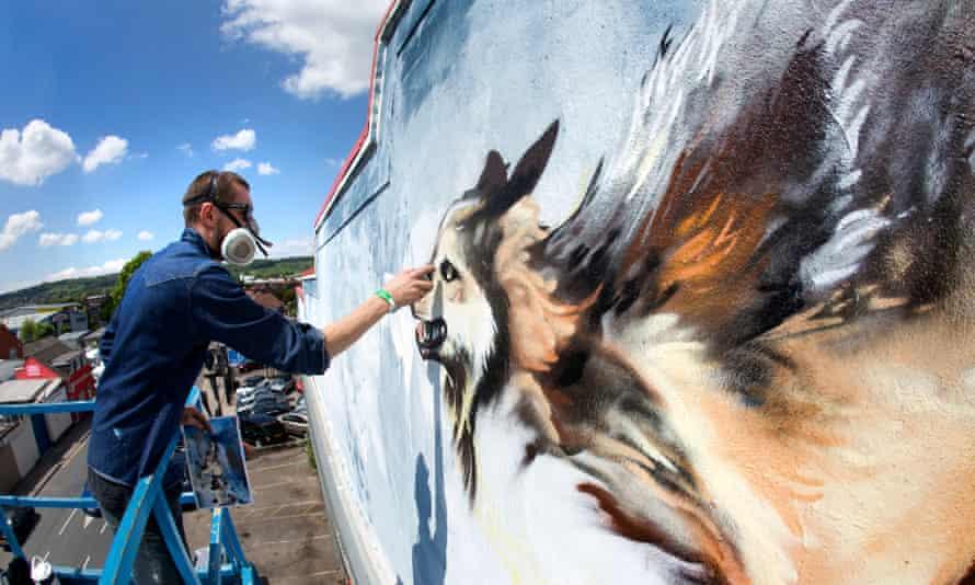 An artist working on street mural as part of Upfest, Bristol