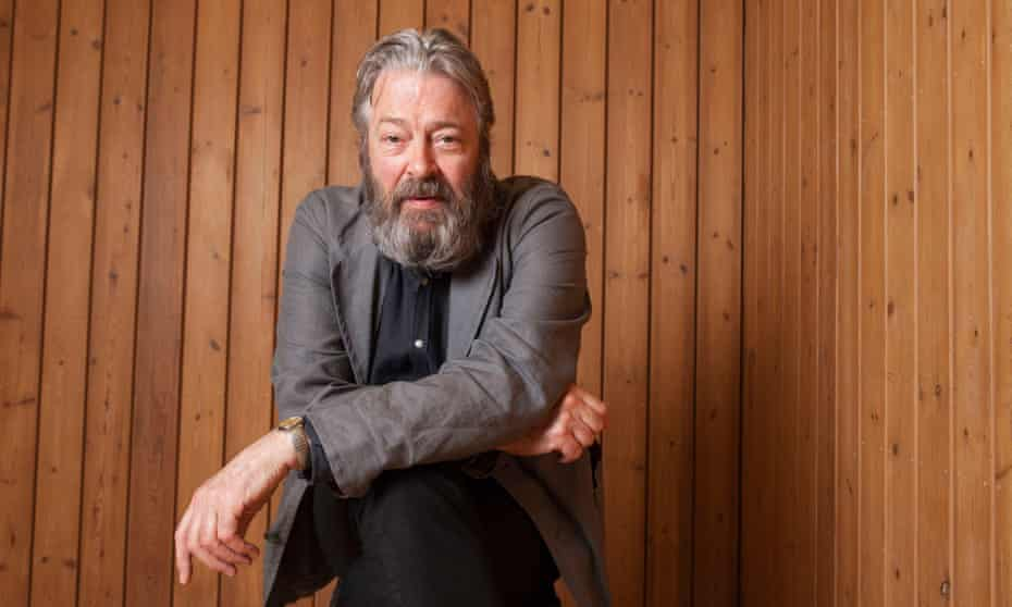 Roger Allam, actor, staring directly at camera, resting his arm on his leg, with wood-lined background.