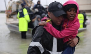 Evacuees are helped to dry land after their homes were inundated with flooding from Hurricane Harvey.