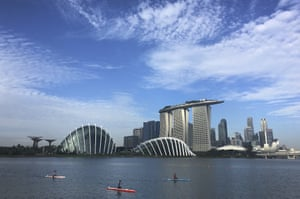 SingaporeKayaks are dwarfed against the skyline of the Marina Bay, which is home to popular hotels, and tourist attractions