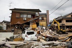 An excavator clears up debris next to a damaged house in Hitoyoshi, in Kumamoto prefecture