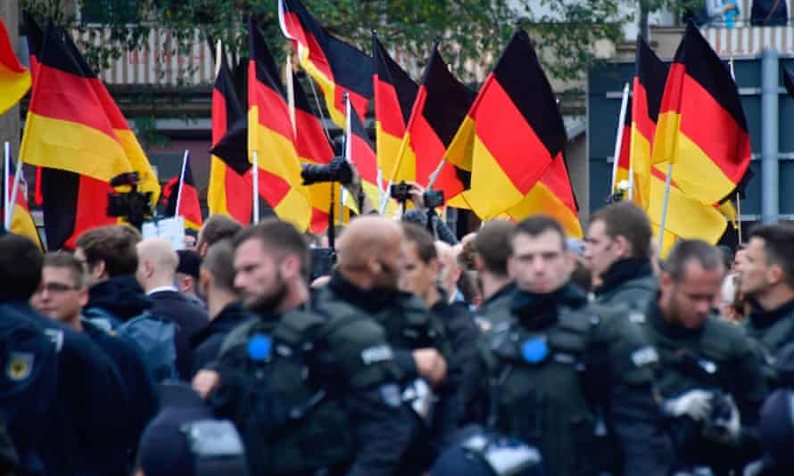 Supporters of the AfD party wave German flags as they walk behind police during a demonstration in Chemnitz, Germany, October 2020.