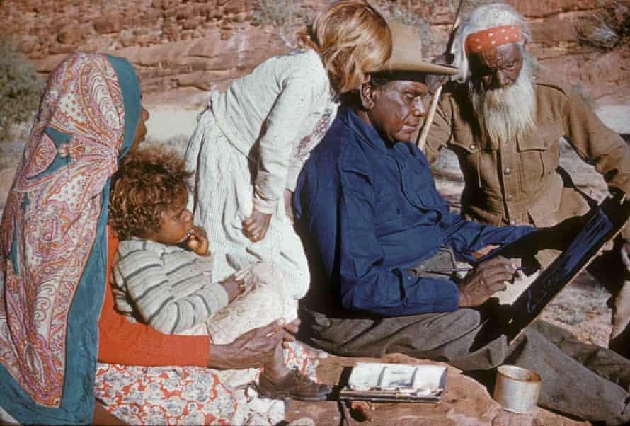 Albert Namatjira's family members watch him as he paints.
