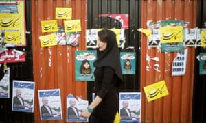 A woman walks past electoral posters in downtown Tehran.