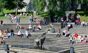Students relaxing in the sunshine on campus at the University of East Anglia in Norwich.