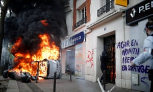 A car burns outside a Renault garage during clashes in Paris.