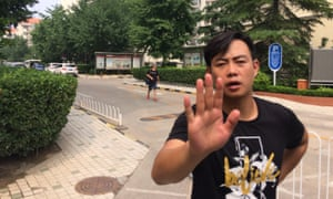 A plainclothes agent outside the Beijing apartment of Liu Xia, the wife of the late dissident Liu Xiaobo.