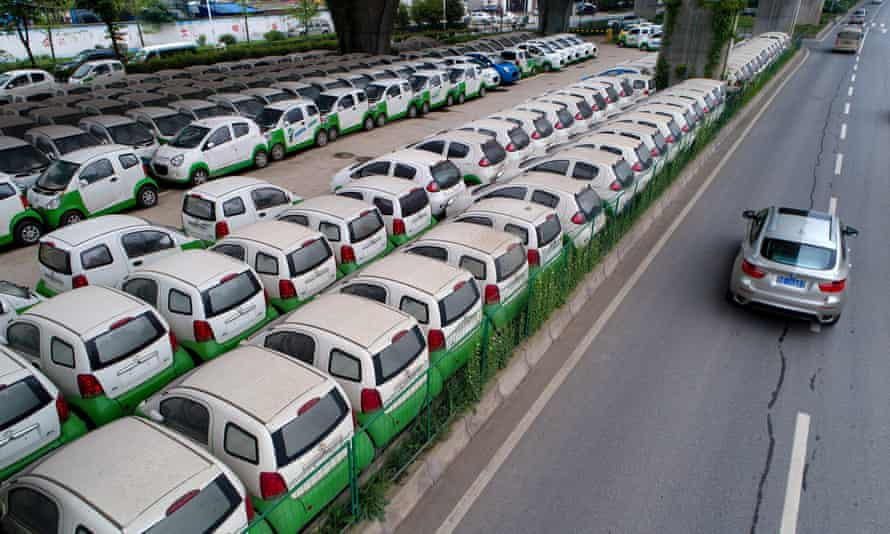 A car passes new electric vehicles in Wuhan, Hubei province