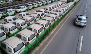 Electric vehicles in a parking lot under a viaduct in Wuhan, central China's Hubei province. Beijing is encouraging drivers to buy electric as it attempts to tackle the country's smog problems.