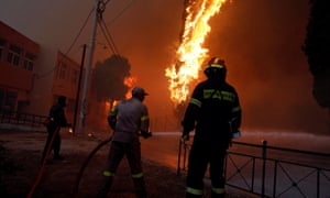 Firefighters and soldiers try to extinguish a wildfire in Rafina, near Athens