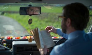 Teacher sitting in the driver's seat of his parked van, reading a book