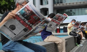 People read the Apple Daily newspaper at Status Square in Hong Kong as part of a silent protest