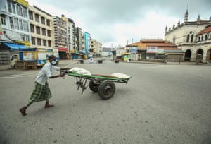 A man pushes a cart along a deserted street in Colombo, Sri Lanka
