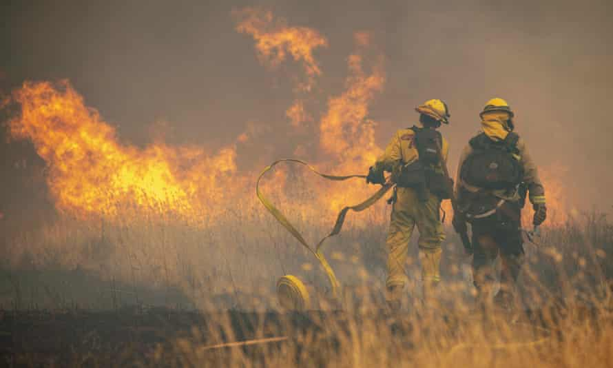 Firefighters battle spot fires in a field in High Valley near the town of Clearlake Oaks.