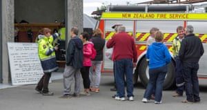 Members of the public gather by the Hanmer Springs Civil Defence information board.