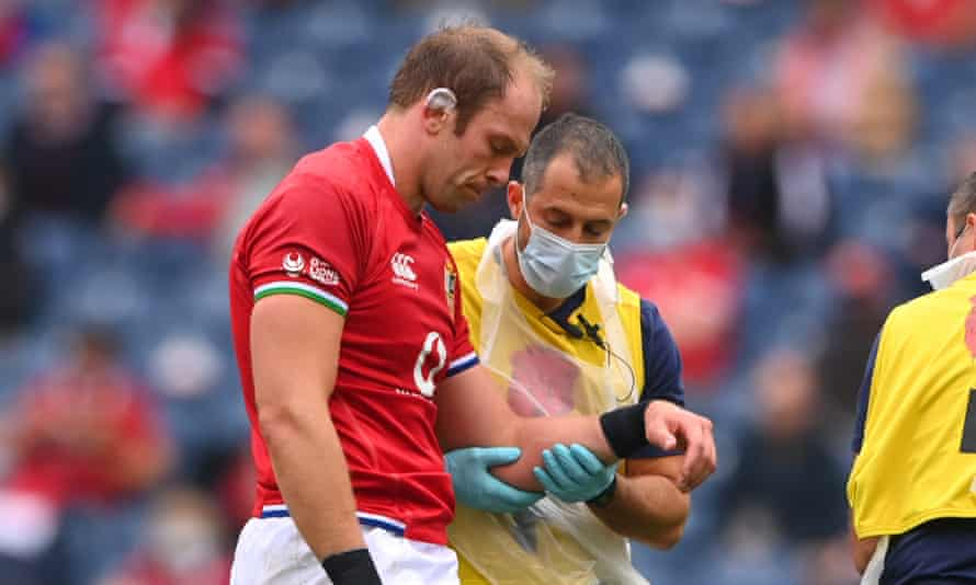 Alun Wyn Jones is led from the pitch by medics at Murrayfield.