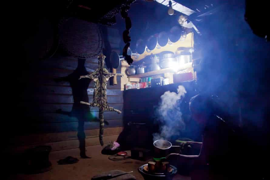 Clouded leopard skin hanging inside a kitchen belonging to a Naga headman, with a woman cooking nearby in 2011.