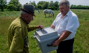 A voter in Szentkiraly casts his vote at in a mobile voting urn.