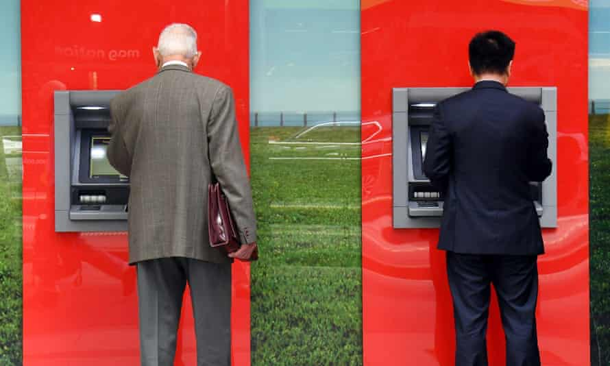 Two people use ATMs