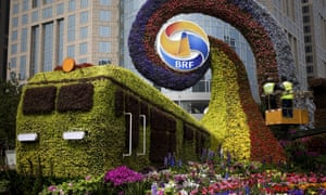 Workers on a platform install flowers on a decoration in a shape of a train for promoting the upcoming Belt and Road Forum in Beijing