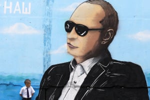 A boy stands by a wall sprayed with a graffiti depicting Russia's President Vladimir Putin in the Crimean city of Simferopol on September 1, 2015