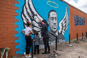 """Houston, Texas, US Pure compassion turns Floyd into an angel in this mural. Its grey stonelike tones and winged bust make it reminiscent of early American gravestones. It is a religious monument, paying its passionate respects to a martyr. The people seen here are making an emotional as well as a physical connection with the work, which has the feel of popular Christian art, complete with its unembarrassed declaration that the suffocated man is """"forever breathing in our hearts""""."""