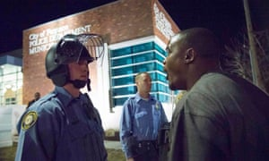 A protester confronts a police officer outside the Ferguson police department.