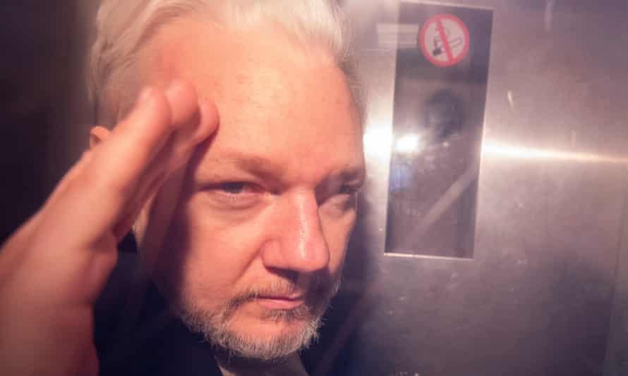 Julian Assange gestures from inside a prison van