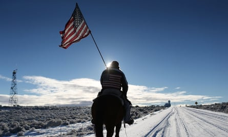 Duane Ehmer carries an American flag as he rides his horse, Hellboy, at the occupied Malheur National Wildlife Refuge on January 15, 2016 near Burns, Oregon.