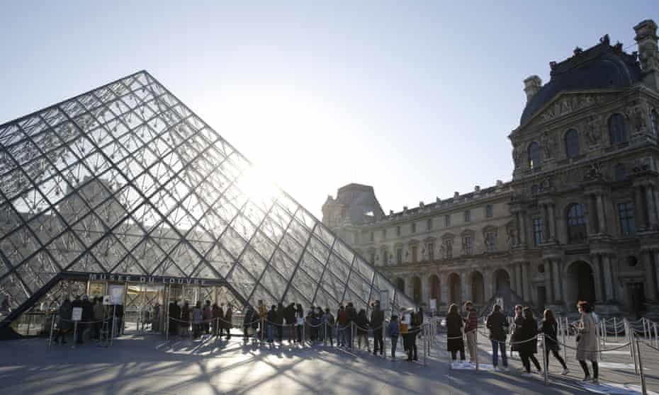 Visitors queue for the Louvre museum in Paris.