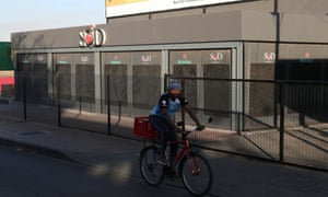 A man cycling past a closed restaurant in Soweto, South Africa last month.