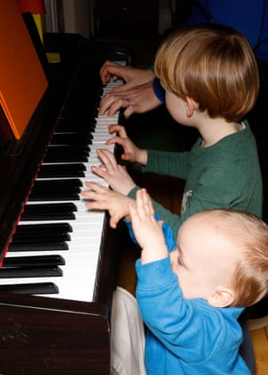 The boys try to play the piano.