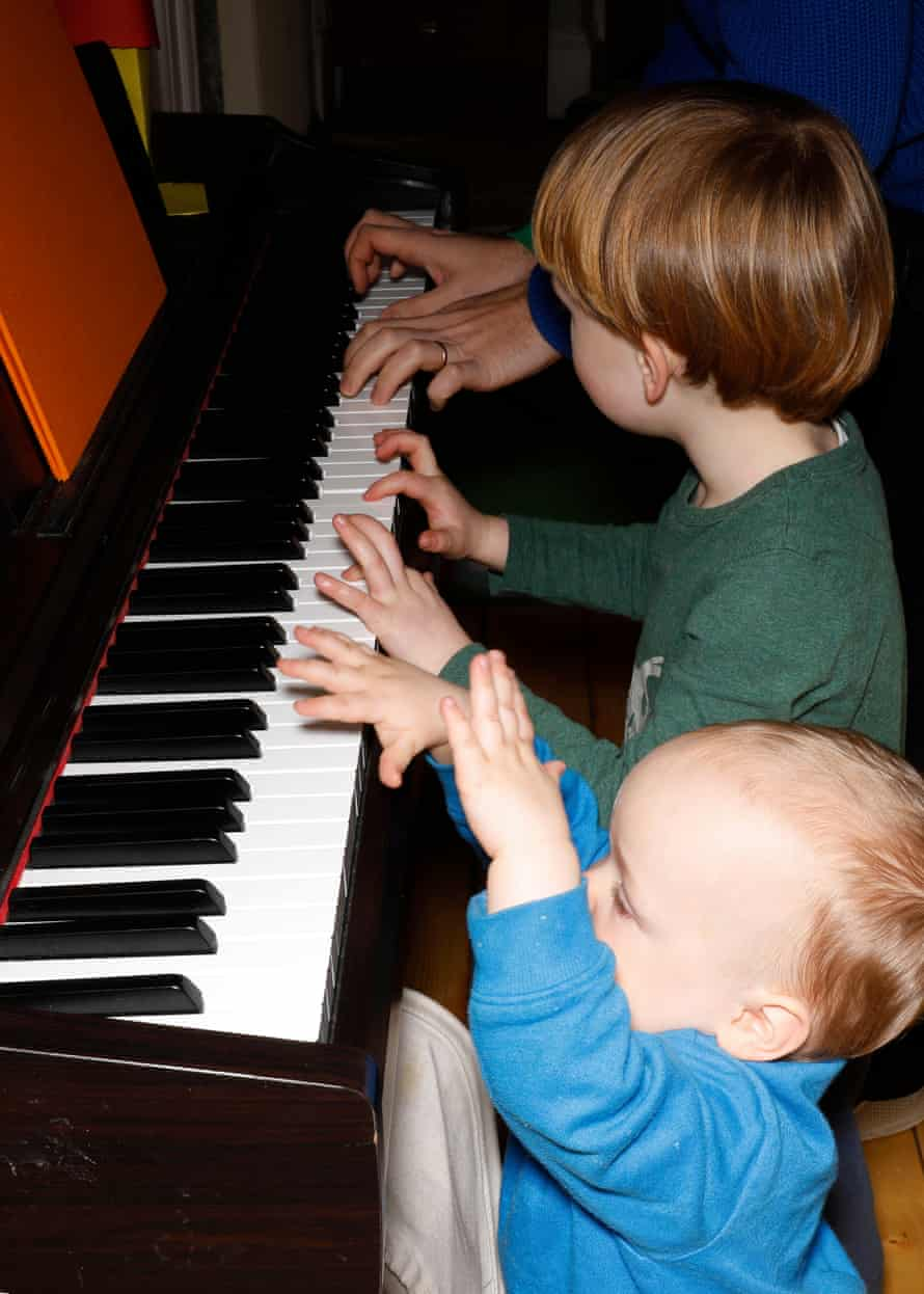 The boys try their hands at playing the piano.