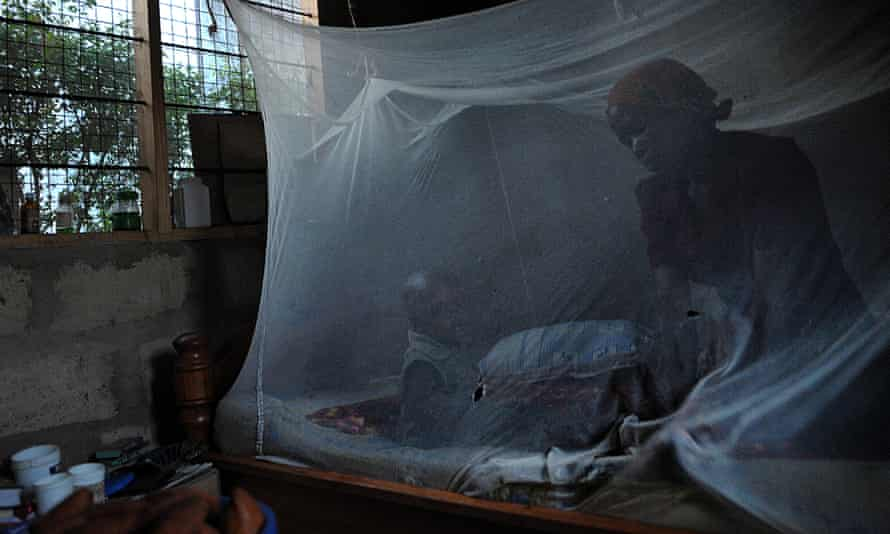 A mother and child sit on a bed covered with a mosquito net near Bagamoyo, north of the Tanzanian capital Dar es Salaam. A new initiative aims to tackle Africa's health challenges.