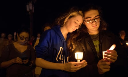 A woman puts her head on a man's shoulder during a vigil held across the street from the First Baptist Church.