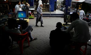 Men sit at their computers waiting to load media files into mobile phones for customers in the Abpara market in Islamabad, Pakistan