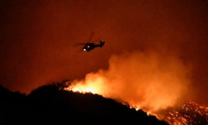 A firefighting helicopter over the Getty Fire north-west of downtown Los Angeles last night