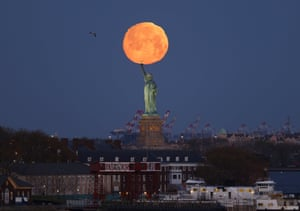 The supermoon sets behind the Statue of Liberty in New York City, USA.