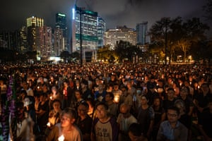 People hold candles as they take part in a candlelight vigil at Victoria Park, Hong Kong