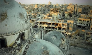 The battle-scarred Khalid ibn al-Walid mosque looms in front of the devastated city of Homs.